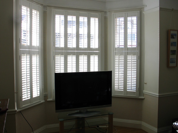Tier-on-tier, bi-fold plantation shutters in wood with 47mm louvres