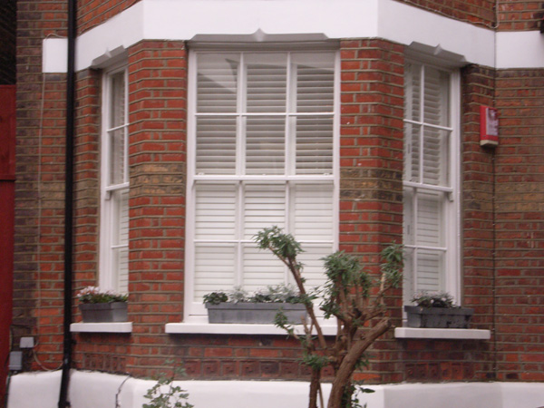 Painted wood plantation shutters in silk white with 63mm louvres - internal and external views