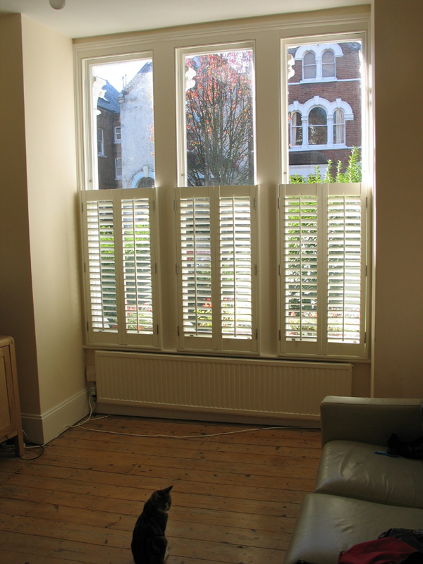 Internal and external views of cafe / half height plantation shutters in silk white with 47mm louvres