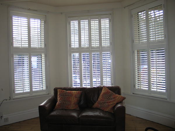 Interior and exterior views of tier-on-tier plantation shutters with 63mm louvres in silk white.